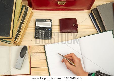 Financial concept. Businessman counting profit and losses analyzing financial results. On a wooden table books documents calculator red briefcase.