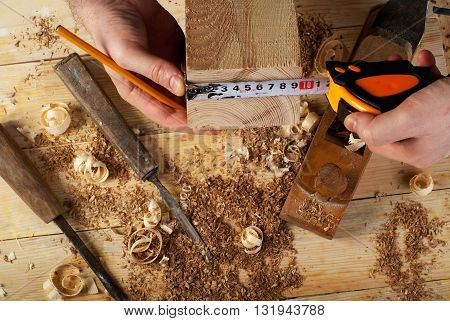 Carpenter working hammer meter and screw-driver on construction background.