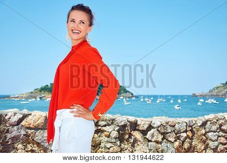 Smiling Woman In Front Of Scenery Overlooking Lagoon With Yachts