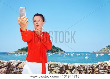 Woman Blowing Air Kiss And Taking Selfie In Front Of Lagoon