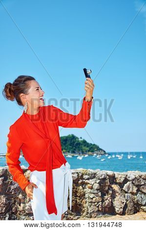 Woman Taking Photo With Digital Camera In Front Of Lagoon