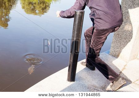 fisherman pulls out of the river carp on summer day