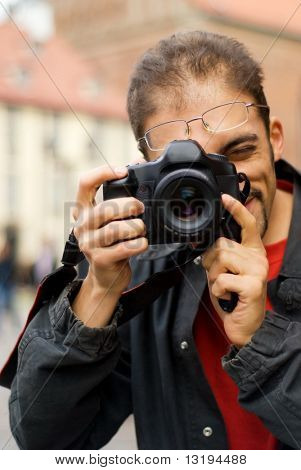 Handsome guy with a digital camera (shallow DoF, focus on eye)