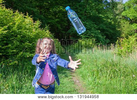 girl in a blue denim jacket catching a plastic bottle with water outside