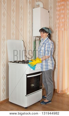 young smiling woman washes a gas stove indoor