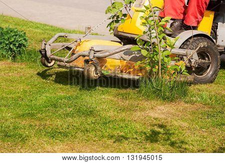 man mows a lawn mower outside closeup