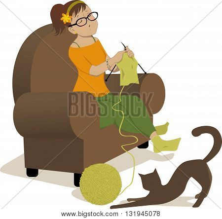 Woman knitting in an armchair and cat playing with a ball of yarn
