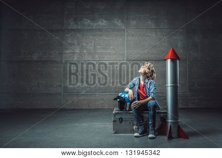 Little boy with rocket in studio