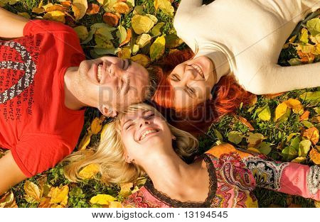 Three friends lying on autumn leaves
