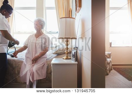 Indoors shot of senior woman's blood pressure being measured by nurse in nursing home. Home caregiver testing blood pressure of old woman.