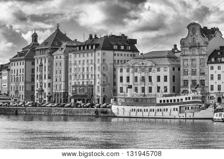 STOCKHOLM SWEDEN - MARCH 30 2016: Old buildings on the shore of the Stockholm harbor from Sweden in black and white