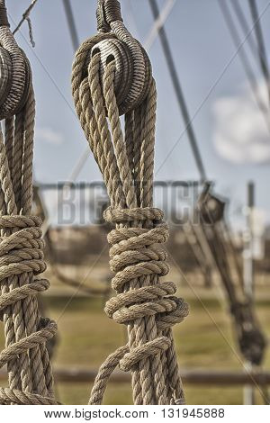 Blocks and tackles on a sailing vessel. Vintage marine ropes and wooden tackle block on sailing vessel.