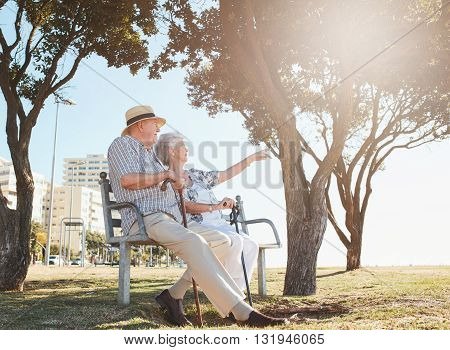 Retired Couple Taking A Break And Relaxing On A Bench
