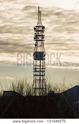 Telecommunication tower with dish and mobile antennas at sunset. Silhouette telecommunication tower at sunset.