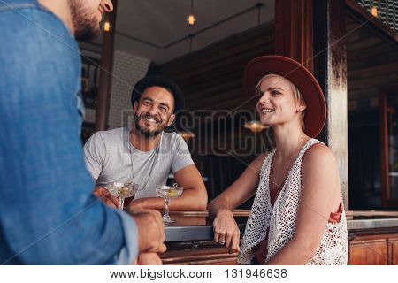 Group Of Young Friends Sitting And Talking At A Cafe