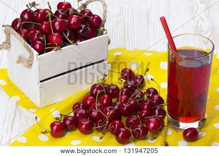 Juice and red cherries in a wooden box on wooden desk