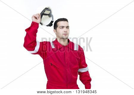 Serious Male Construction Worker with short black hair in red uniform holding safety helmet - Isolated. Industrial worker in red uniform holding hardhat isolated on white.