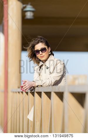 portrait of middle-aged woman on balcony over sea. beautiful young woman enjoying the freshness of the morning on the balcony