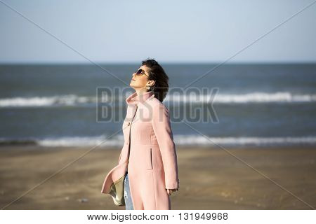 Portrait of attractive young woman with long beautiful hairs dressed pink coat, which posing in autumn Caspian sea beach. Happy fashion woman profile breathing deep fresh air in winter on the beach