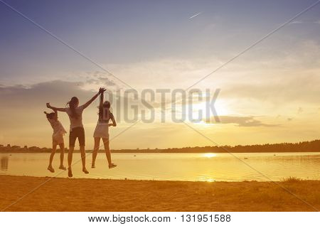 Bouncing mother and her daughter by a lake at sunset