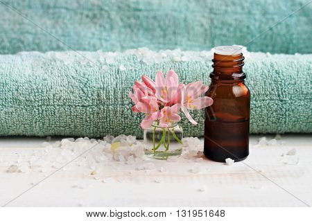 Aroma care spa background. Ethereal oil apothecary bottle, bathroom towel, flowers, salt.