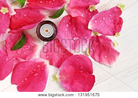 Essential rose oil bottle, pink fresh petals water-drops scattered background, top view, aromatherapy spa. Shallow focus on bottle, flowers naturally blurred.