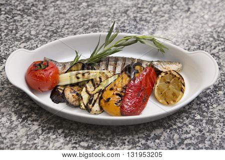 grilled fish with vegetables. Smoked fish on plate on wooden table