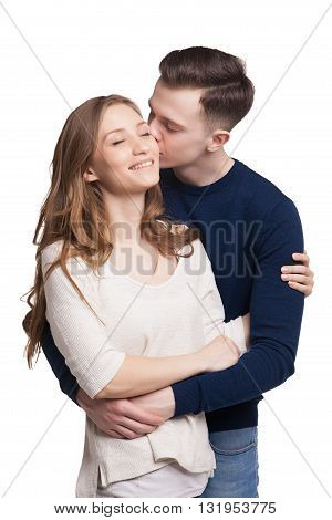 Portrait of young man kissing his girlfriend while hugging her.Girl smiling with eyes closed.