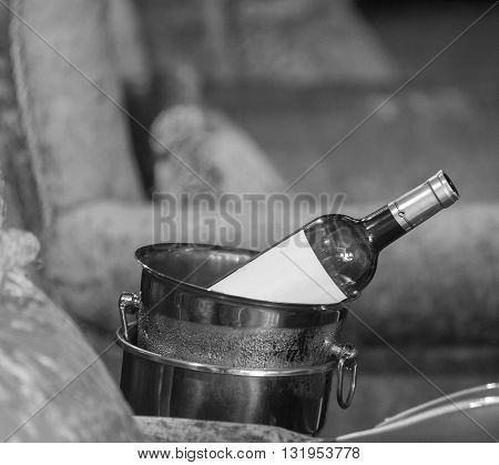 Wine bottle in a bucket with ice on the couch. Black and white photo.