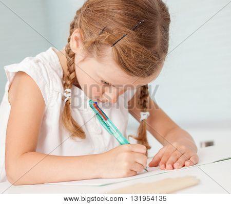 Little child writing. Preschool girl doing homework