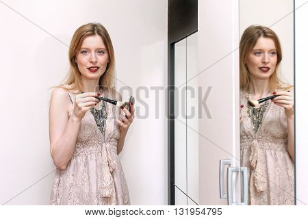 Young beautiful girl getting ready in front of a mirror