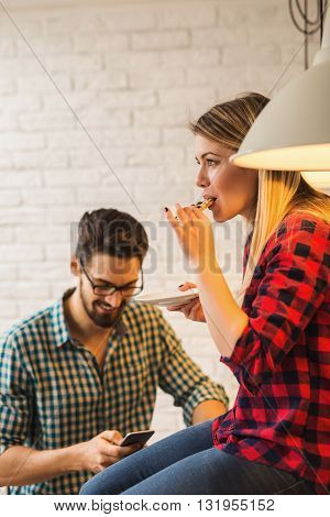 Woman eating a cookie while her boyfriend is surfing the net
