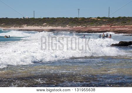 KALBARRI,WA,AUSTRALIA-APRIL 20,2016: People jumping the foamy waves and body boarding in Indian Ocean waves at Jake's Point in Kalbarri, Western Australia.