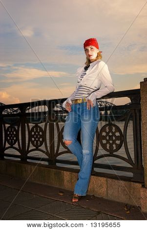 Beautiful young girl in red bandanna over sunset sky