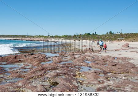 KALBARRI,WA,AUSTRALIA-APRIL 20,2016: Tourists walking the rocky reef on the beach at Jake's Point with the Indian Ocean and coastal dunes on a clear day in Kalbarri, Western Australia.