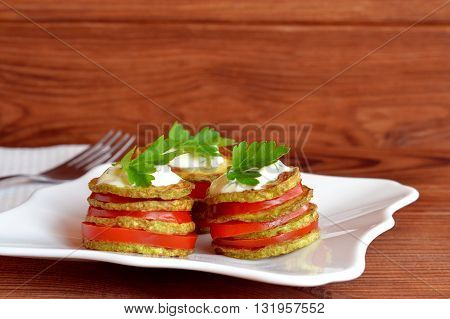 Fried zucchini with fresh tomatoes, yogurt and parsley. Fried zucchini appetizer recipe. Easy vegetable snack. Roasted yellow squash in olive oil. White napkin, fork, wooden table. Closeup