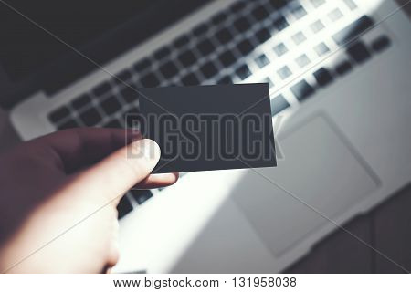 Image Man Showing Blank Black Business Card and Using Modern Laptop Blurred Background. Mockup Ready for Private Information. Sunlight Reflections Surface Gadget. Horizontal mock up