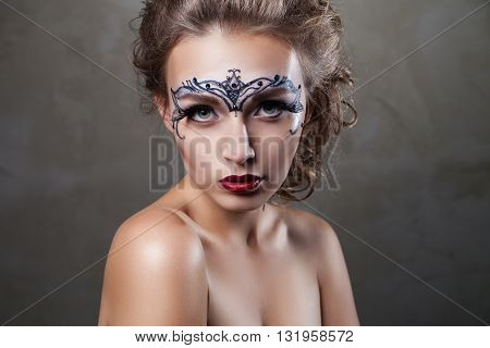 Ornamental face art.Headshot of beautiful model looking at camera.Studio shot
