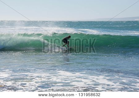 KALBARRI,WA,AUSTRALIA-APRIL 20,2016: Surfer in the turquoise waves of the Indian Ocean at Jake's Point in Kalbarri, Western Australia.