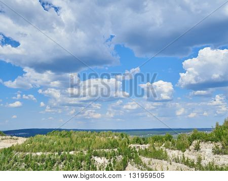 The sky with clouds and forest on the horizon.