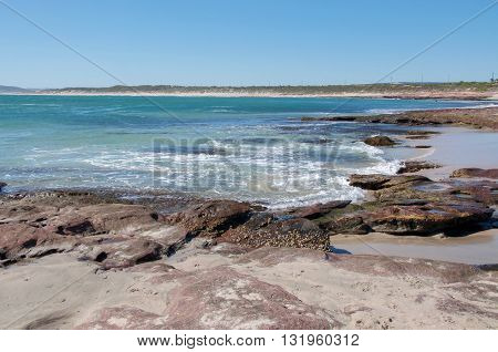 Turquoise Indian Ocean seascape with sandstone rock formations on the beach at Jake's Point in Kalbarri, Western Australia on a clear day.