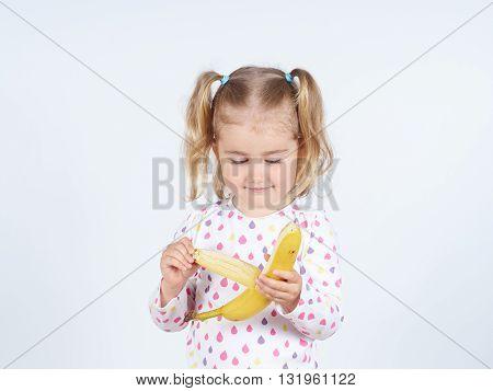 Little Girl Eating A Fresh Banana.