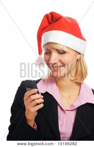 Beautiful business woman in Christmas hat typing message on her mobile phone