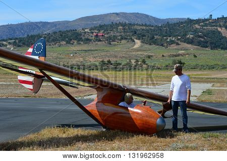 TEHACHAPI, CA - MAY 28, 2016: Jeff Byard discusses his flight with a ground crew member after landing his Bowlus glider during the Western Vintage/Classic Regatta.