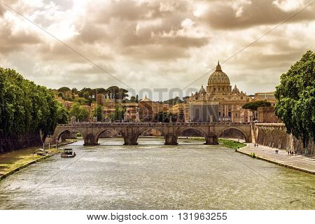 Tiber river, Ponte Sant'Angelo and St. Peter's cathedral by cloudy day, Roma, Italy