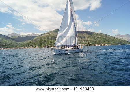 Tivat, Montenegro - 26 April, The yacht under white sails on a background of mountains, 26 April, 2016. Regatta