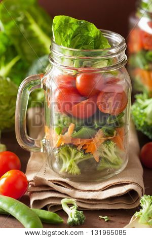 healthy vegetable salad in mason jar. tomato, broccoli, carrot, pea