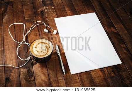 Blank stationery on vintage wooden table background. Blank paperwork mock-up. Blank letterhead pen headphones and coffee cup. Blank template for branding identity.