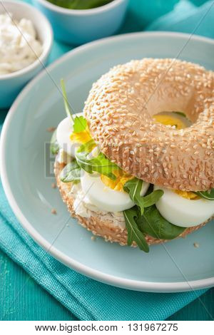 breakfast sandwich on bagel with egg cream cheese arugula