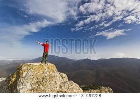 man standing on a cliff in mountains with snowy picks and blue sky with clouds on background